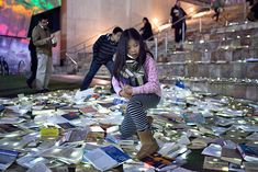 "Over 10,000 books thrown out by public libraries were recently given new life in a beautiful new lighting installation by Inhabitat favorites Luzinterruptus. Called ""Literature Versus Traffic"", the installation spilled out into the streets of Melbourne during the Light in Winter festival, fusing discarded books with glowing LED lights. The river of glowing books invited passersby to leaf through the volumes that had been forsaken for the dump and take them home."