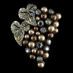 Ca 1950s Schiaparelli grape cluster brooch formed by cultured pearls and rhinestones; lg. 3 in. Elsa Schiaparelli (Italian, 1899-1973) was a fashion designer whose greatest rival was Coco Chanel. In the time between the two World Wars, Schiaparelli was regarded as one of the most prominent fashion designers in the world.