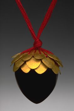 "Julia Turner ""Gold Leaves"" pendant, 2002. Ebony, 24k gold, silk. Photo by George Post. .8 x .6 x .6 in (2 x 1.5 x 1.5 cm)."