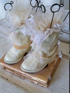 If allowed could place old boots decorated in pearls and lace or just filled with gyp. Could go on stairs in courtyard or on floor near doors quirky way of bringing things together.