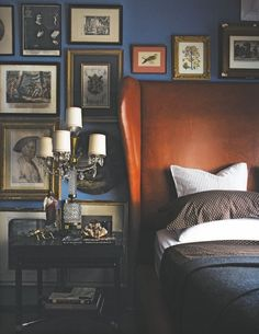 Gallery wall surrounding headboard, leather against navy walls