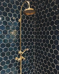 A geometric tile in dark green looks stunning used in a shower enclosure and creates a dramatic look.