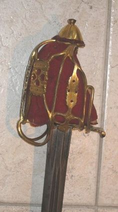 "Very Rare and Desirable Scottish Colonels/ Generals Officers Basket Hilted Broad Sword with Gold guilt Basket hilt, 85% gold guilding remaining. Comprising connecting junction pannels pierced with hearts and circles and cut with scalloped edges, fluted domed pommel, with it's original crimson and buff leather liner, shark skin wire wrapped grip 33"" double fullered blade (un-marked) basket has a good working life repair C. 1790-1810"