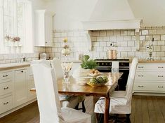 This kitchen looks so comfortable to cook in. I love the high ceilings and the subway tile, and the tidy wooden table in the centre.