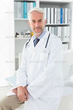 Portrait of a smiling confident male doctor standing at the medical office - Sto. Portrait of a smiling confident male doctor standing at the medical office - Stock Photo - Images
