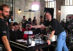 Matthew Irving (cinematographer) measures the light as Jaime King, Leigh Whannell, and Tim Guinee prepare for an intense court scene.