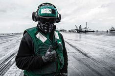 An air department Sailor on the flight deck of the Navy's forward-deployed aircraft carrier, USS Ronald Reagan. The Ronald Reagan, Theodore Roosevelt and Nimitz strike groups are underway and conducting operations in international waters as part of a three-carrier strike force exercise.