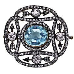 CARL FABERGE Aquamarine Diamond Eternity Brooch. 1899-1908.  Designed as an open work plaque, the central collet-set aquamarine surrounded with four arrows forming a circle, each arrow highlighted with an old brilliant-cut diamond, the frame shaped as two interlaced loops set with rose-cut diamonds.