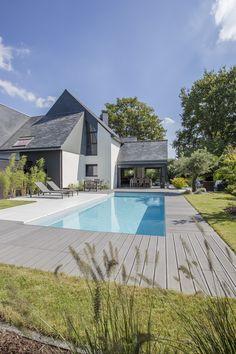 L'esprit familial par l'esprit piscine  9 x 3,50 m Revêtement gris clair Escalier d'angle avec banquette Margelles et plage en dalle et bois composite