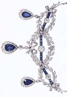 A BELLE ÉPOQUE DIAMOND AND SAPPHIRE BROOCHPENDANT, BY LACLOCHE. Designed as three old brilliant-cut diamond collets on a calibré-cut sapphire bar within an entwined diamond set garland border suspending three pear shaped sapphire and diamond cluster drops, on a detachable trace link chain, circa 1905.