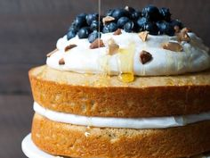 A soft lemon cake made with Greek yogurt and olive oil is layered with a soft, sweet coconut whipped cream and fresh blueberries. Make this simply stunning spring cake for an easy dessert to impress your guests.