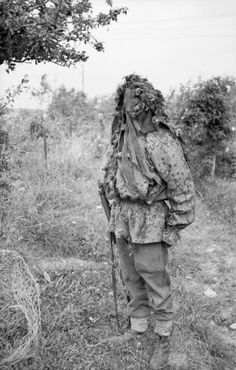 A British sniper demonstrates his camouflage at a sniper school in a French village, 27 July 1944. He is wearing a captured Waffen-SS camouflage smock.
