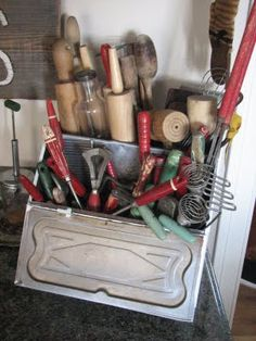 A collection of vintage kitchen utensils in old metal box.