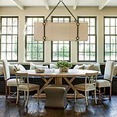 Spread Out - Gather 'Round the Dining Room Table - Southernliving. This table's soft oval shape, distinctive base, and light finish are even more striking when juxtaposed with the dark upholstery and sharp angles of the 14½-foot-long banquette. Three other seating styles offer variety to the room, while an enormous chandelier with iron detailing draws the eye up.     See more of this Home with a Neutral Color Scheme