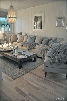 A gorgeous and cozy living room draped in shades or gray and blue. There's a beautiful chandelier hanging above wood laminate floors. Click to see our laminate flooring guide.