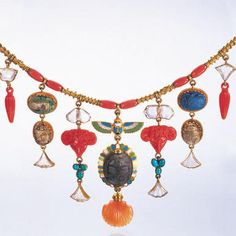 Coral and cylindrical gold link mid-Victorian Egyptian revival fringe necklace, Hancock's & Co, late 1870's. Each link with varying bead and wirework decoration, suspending seven graduated fringe pendent drops; central drop with a blue, green and white enamel winged scarab, w/ a large glazed composition scarab below, within a similarly decorated border with carved fluted cornelian shell terminal, pendent drops either side suspending carved coral rams heads, glazed composition scarabs, fluted…