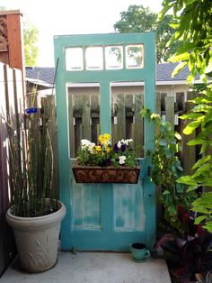 """My Secret Garden Door...    Free door! Painted white & turquoise then distressed. Added window box & training grapevine to  grow over it.  Needs a vintage doorknob.  -> Strategically use as a neighborly """"privacy screen"""".  -> Anchored into cement (doesn't lean on neighbors fence & won't get stolen)"""