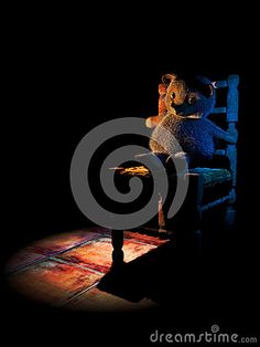 Crying teddy bear on a wicker chair in the dark. Abstract presentation symbolising children abuse, tortures and mistreatment.