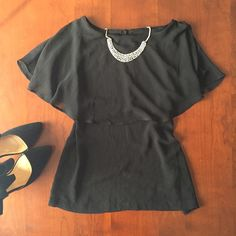 Tiered black tank top Charming black sleeveless blouse with tiered layer over top shoulders. Has a small keyhole and button closure in the back. 100% polyester. Never worn. H&M Tops Blouses