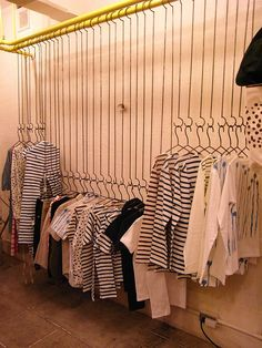 Effective use of line // creates variety in the levels of hanging clothing items // industrial feel.