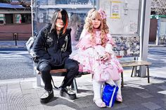 Mad Punks x Angelic Pretty in Harajuku  Contrasting Harajuku kids sitting on a bus bench in front of Harajuku Station this afternoon.