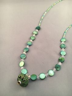 This necklace has a unique metal green pendant with flat green stones. Matching earrings and 2 bracelets