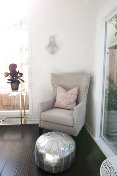 A silver ottoman, tall lounge chair, and crystal sconce give this corner a moment of luxury.