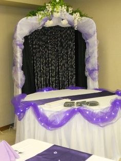 Purple and white cake table w/arch.  Designed and decorated by Decorative Essentials of West Branch, mi
