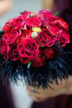 A cuff of black feathers surrounds this bouquet of red roses and ranunculus.