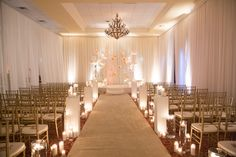 White, Vintage Wedding, Candles, Indoor Ceremony at The Villa, Westminster.  walkway with columns.  gold chiavarri chairs.  ivory satin back drop.  pin wheel design.  chandelier.