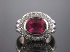 14kt White Gold Dome Ring Consisting Of 1 Bezel Set Oval Shaped Tourmaline Weighing 2.63 Carats Surrounded By 1 Row Of Round Brilliant Cut Diamonds Having A Total Weight Of .45 Carats.