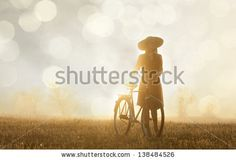 Girl and on a bike in the countryside in sunrise time by Masson, via Shutterstock
