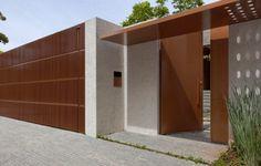 Fachada com portões de ferro pintados de marrom e muro de alvenaria com textura clara. Projeto Carolina Rocco