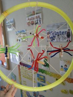 My Spiders and spiderweb for the theme #Minibeasts!   The spiders are made with pegs and pipe cleaners and then we stuck on eyes and pom poms!   The web is made from a Hula hoop and string!  The kids love it!!