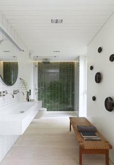 This modern bathroom is decorated with white and green wall tiles and a stylish bench by Hans J. Wegner. The hooks in glass are by Tom Dixon.