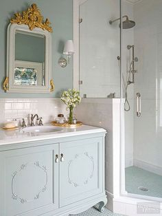 Vintage bathrooms often take a charming cottage turn. This one features a pretty vanity built from a repurposed dresser, a surf-and-sky palette, and crisp white surfaces. Gilded touches add chic shimmer, which underscores the room's collected appeal./