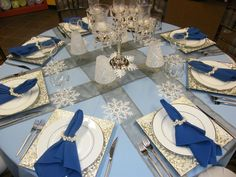 nappe de table bleue à motifs flocons de neige, serviettes bleues avec des anneaux de perles blanches