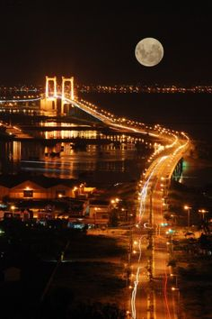 full moon over lighted bridge and bay