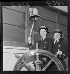 Two unidentified women in Royal New Zealand Naval Service uniforms, probably in Wellington, including a HMS bell and a steering wheel 1959