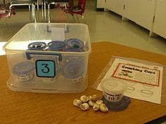 Put a different number of objects (shells, beads, rocks, pom poms, buttons, etc.) in each cup. Students count the objects and write the number on the recording sheet.