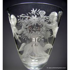 """A Georgian Light Baluster wine glass having a round funnel bowl finely engraved with two winged Putti holding a wreath with two doves below,on the reverse is the inscription Nos Plaisirs Sont Egeaux, """"our pleasures are equal"""",both Putti have beautifully polished wings. http://www.scottishantiquesinc.co.uk/georgian-glass/newcastle-light-baluster/engraved-putti#.U-3BA0jLJOE"""