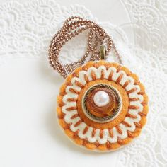 Round Orange and Cream Felt Pendant with Hand Embroidery and Orange Pearl Accent (ball chain included). $18.00, via Etsy.