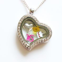 A heart shaped sweet 16th birthday locket for your daughter. This 16th birthday gift for her comes complete with a 16th charm and a daughter charm plus a birthstone and a birthday cake charm!  To change the card featured in the photographs above, please click this link www.memoriesandmoregifts.etsy.com and select the 'BIRTHDAY CARDS' from our main page.  *ITEM DETAILS*  * At a Glance *  • Alloy metal heart locket with rhinestones – magnetic closing • 18 inch Sterling Silver Chain • 16th…