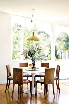 An airy dining room space with tulip table, wood dining chairs and pendant lamp.