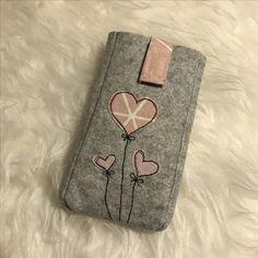 Eine Handyhülle aus Filz und genähmalten Herzchen