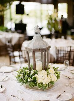 Lanterns with candles and white flowers. Other tables had mercury glass with white flowers.