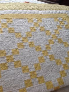 Single Irish chain in butter yellow/white two color quilt full size with tulip quilting motifs and feather border