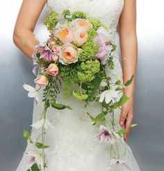 """A cascade bouquet of clematis, pink peonies, peach """"Juliet"""" garden roses and spray roses with accents of green viburnum."""