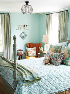 Soft aqua walls and accessories are a breath of fresh air in this bedroom. Accents of warm beige and pumpkin orange break up the tone-on-tone blue color scheme.