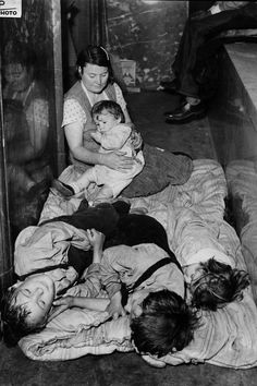 "A mother and children rest as they and over 40 men, women and children camp out at City Hall in St. Louis, Mo., April 29, 1936. When a St. Louis alderman took no action to increase relief appropriations, protesters descended upon City Hall and threatened to stay ""'til hell freezes over or we get relief."" They started their second day in the building today."